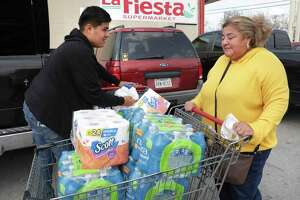 Anna Saenz, right, gets help from son Gabriel Thomas while loading groceries including water and toilet paper Friday, March 13, 2020.
