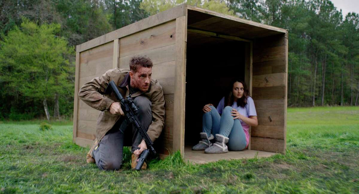 """This image released by Universal Pictures shows Justin Hartley, left, and Sylvia Grace Crim in a scene from """"The Hunt."""" (Universal Pictures via AP)"""