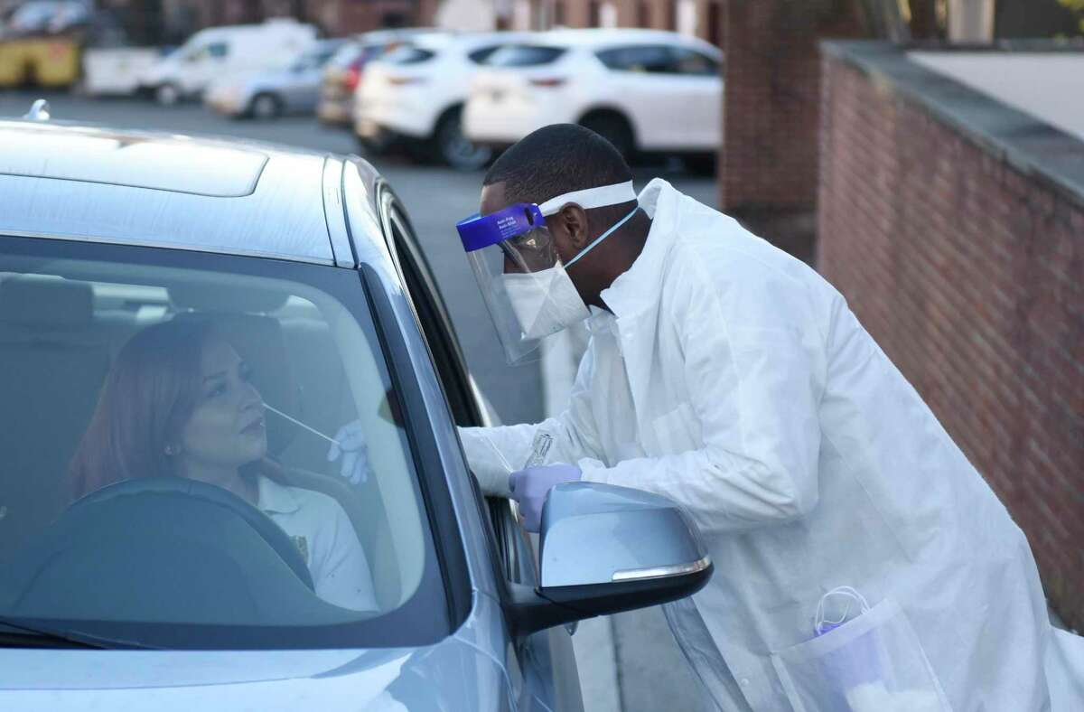 Phlebotomist Warren Dawkins demonstrates drive-thru testing for coronavirus at Murphy Medical Associates in Greenwich, Conn. Monday, March 9, 2020.