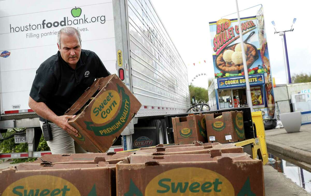 """Dominic Palmieri, a concession owner, loads unused food from the Houston Livestock Show and Rodeo onto a pallet Friday, March 13, 2020, near NRG Stadium in Houston. Vendors donated unused food to local charities, including the Houston Food Bank and the Star of Hope, after the rodeo was canceled due to concerns about COVID-19. """"It's tens of thousands of dollars of food,"""" he said."""