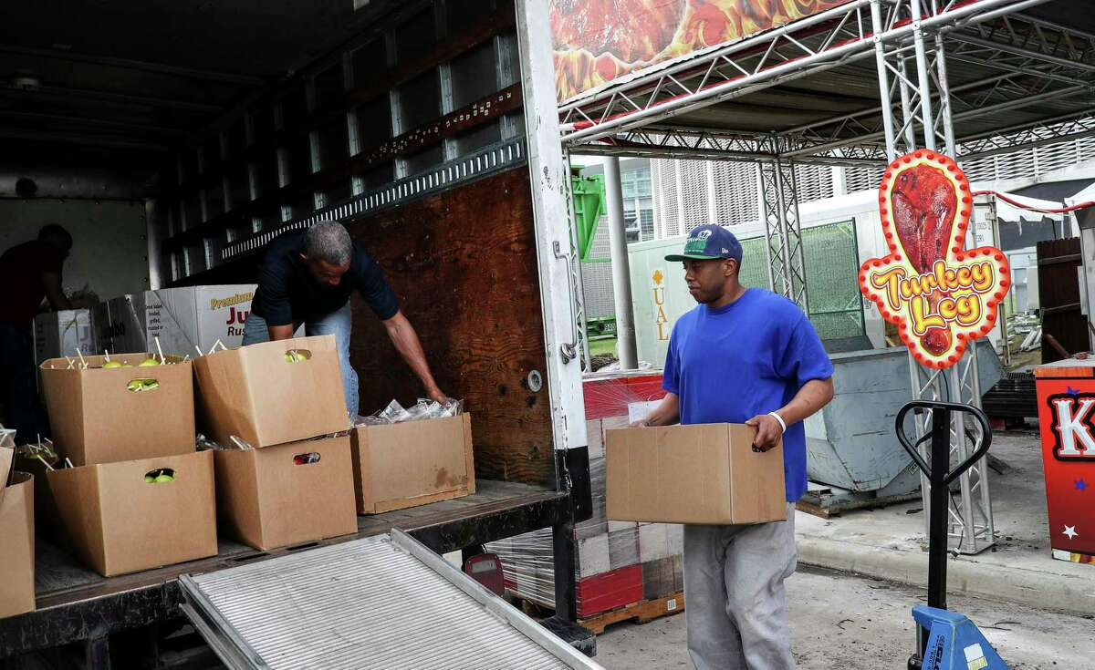 """Aaron Heller, from right, a warehouse worker for the Star of Hope, Thomas Tousant, who described his job as a """"servant of God,"""" and Larry Reynolds, a transportation specialist, load food that was donated to the Star of Hope on Friday, March 13, 2020, near NRG Stadium in Houston. Vendors from the Houston Livestock Show and Rodeo donated unused food to local charities, including the Houston Food Bank and the Star of Hope, after the rodeo was canceled due to concerns about COVID-19."""