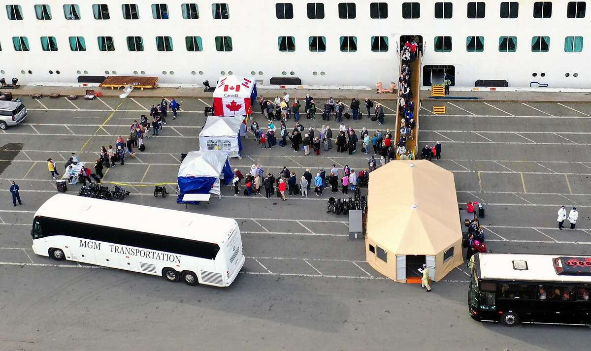 OAKLAND, CALIFORNIA - MARCH 09: Passengers disembark from the Princess Cruises Grand Princess cruise as it sits docked in the Port of Oakland on March 09, 2020 in Oakland, California. The Princess Cruises Grand Princess has been prevented from docking unt