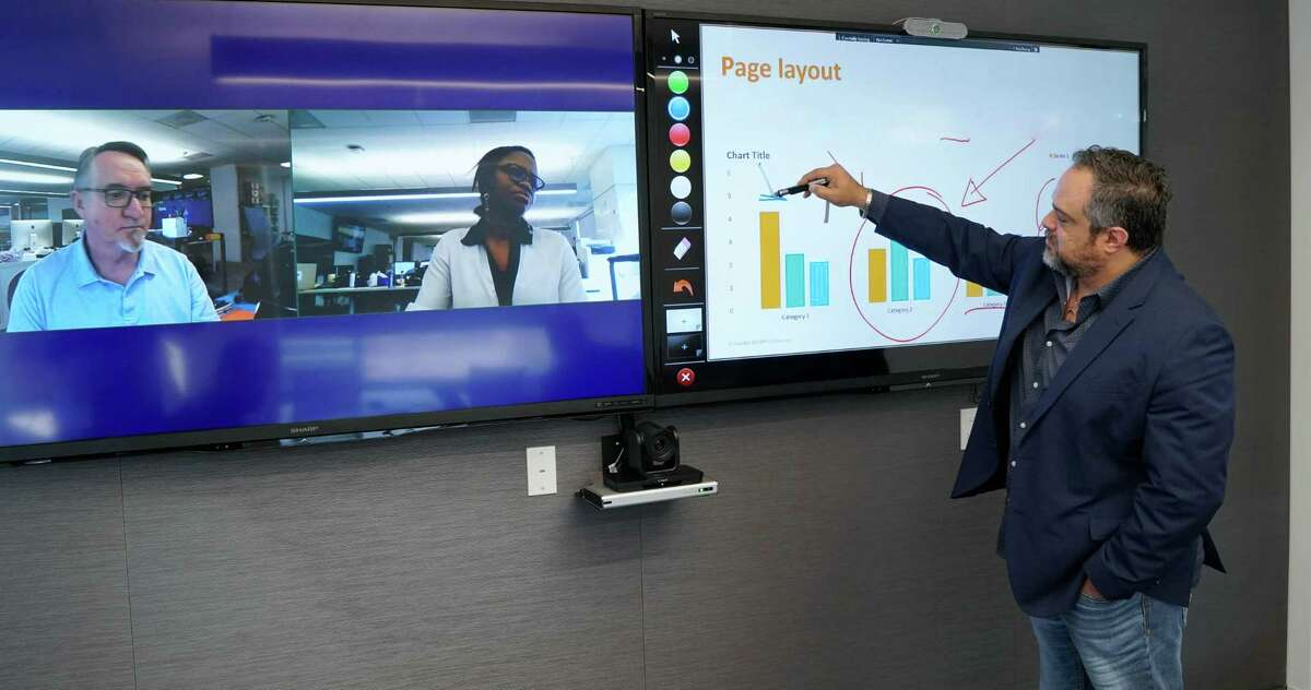 BMC Software employees demonstrate how the company's in-house video conferencing system works.