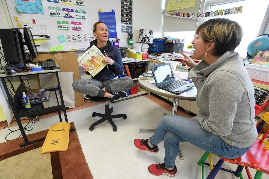 Melissa Wall and Stacey Wood, teachers at Julia A. Stark School in Stamford, Connecticut, collaborate on Friday on their Virtual Lesson plans that students will use while the schools are closed for the next two weeks. Wall and Wood, along with fellow teacher Alex Frattaroli are preparing a Read Aloud, where they as part of their lessons, read a book via a video presentation for their students. Photo: Matthew Brown / Hearst Connecticut Media / Stamford Advocate