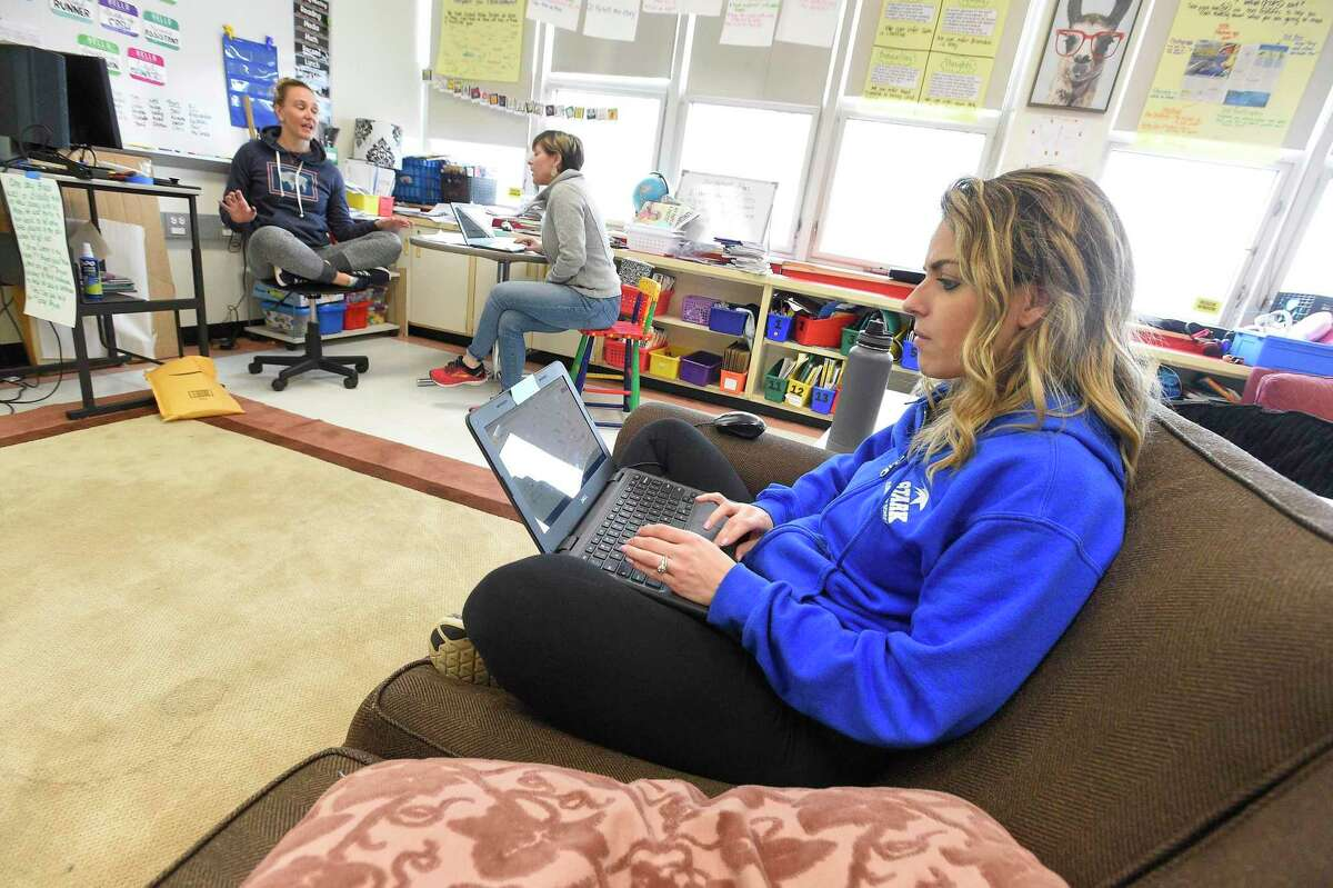 Alex Frattaroli, a third grade teacher at Julia A. Stark School in Stamford on Friday sits on a couch upload digital mathematics lesson plans while fellow teaches Melissa Wall and Stacey Wood collaborate on their Virtual Lesson plans that students will use while the schools are closed for the next two weeks.