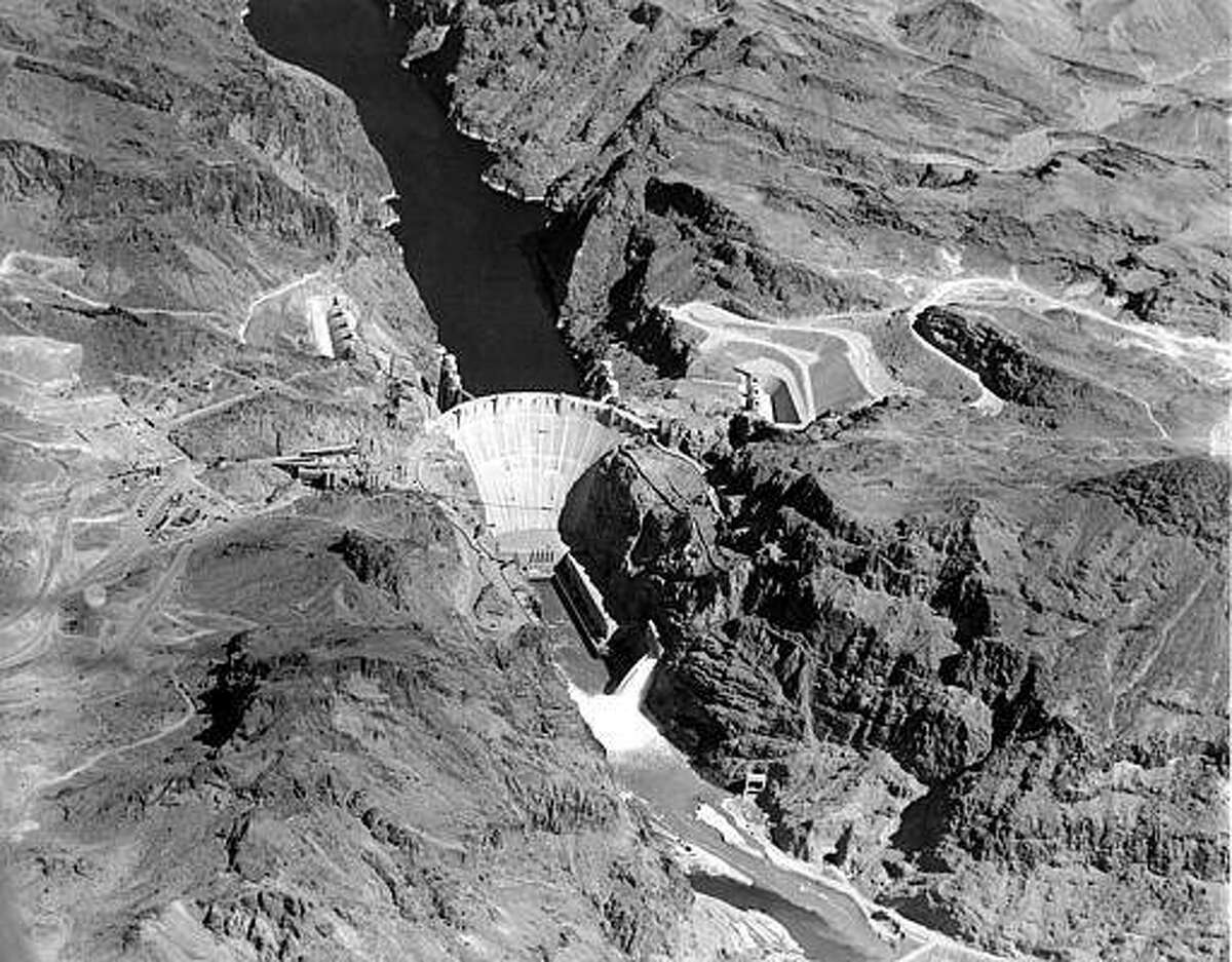 This is an aerial view of the Hoover Dam of the Boulder Canyon project situated in Black Canyon on the Colorado River, on the border of the states of Nevada and Arizona, in Boulder City, Nev., March 13, 1936. A portion of the Mead Lake is shown behind the 731-foot high concrete structure. Water from the lake flows at the ratio of several thousand gallons per second from outlet valves on the Arizona side, below dam. Intake towers are behind the dam on each side. (AP Photo)