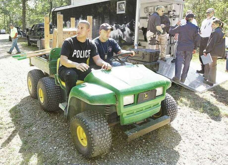 In this September 2010 file photo, Alton Police officers Marcos Pulido, left, now deputy chief, and Seth Stinnett, right, now chief of detectives, head off on an off-road vehicle to search the rural Jerseyville property of Roger Carroll. Photo: John Badman   Telegraph File Photo