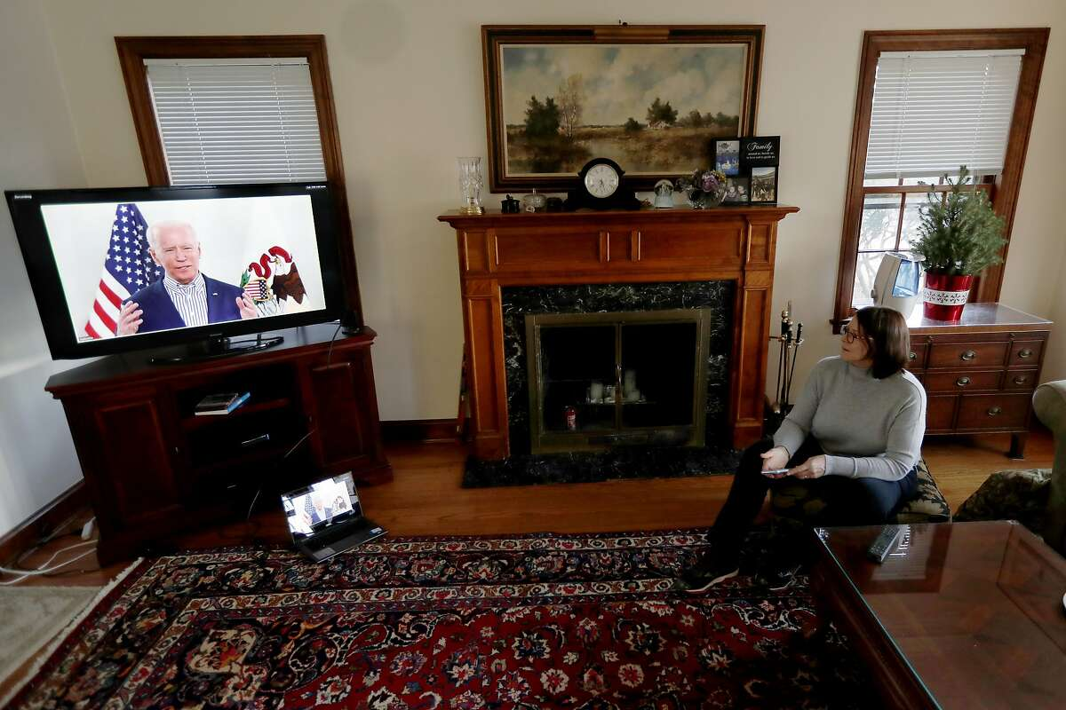 Lally Doerrer watches Joe Biden during his Illinois virtual town hall, in her living room Friday, March 13, 2020, in Chicago. (AP Photo/Charles Rex Arbogast)