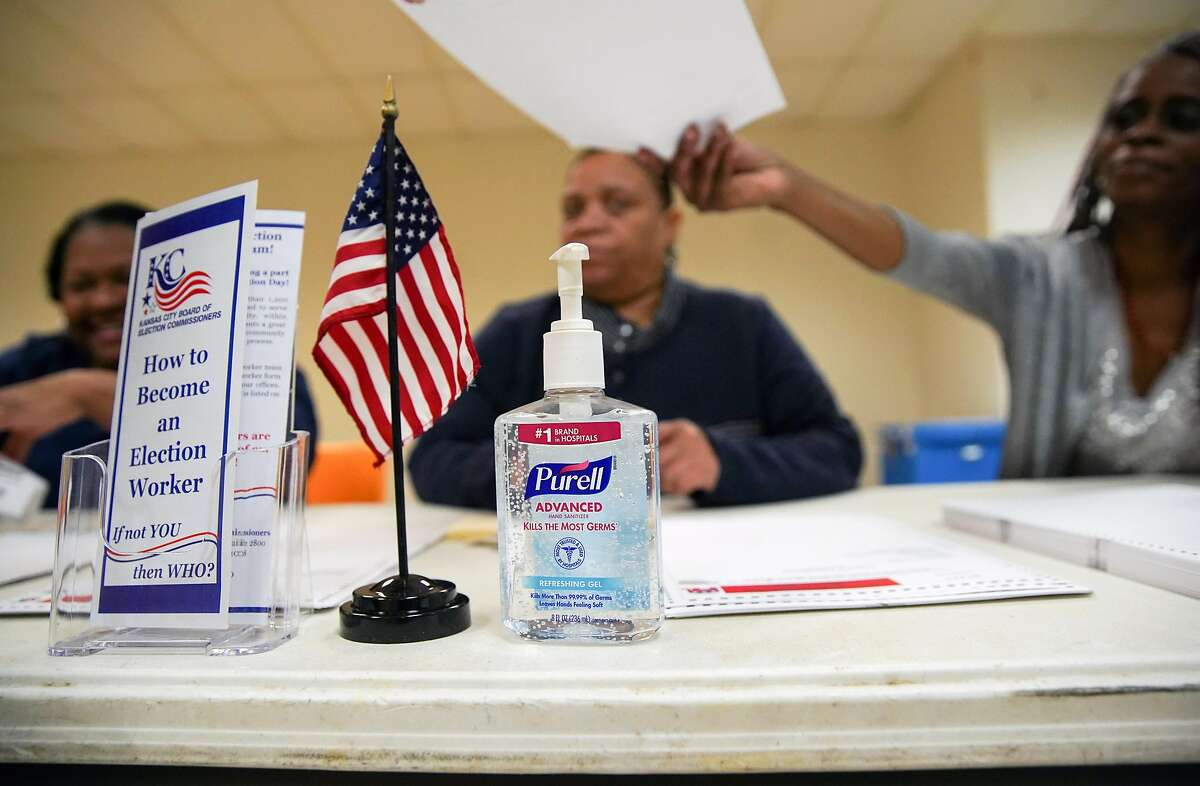 Poll workers keep a bottle of hand sanitizer at the ready as they greet primary voters at a polling place in Kansas City, Mo., on Tuesday, March 10, 2020. Six states are holding nominating contests for the Democratic presidential nomination on Tuesday. (Christopher Smith/The New York Times)