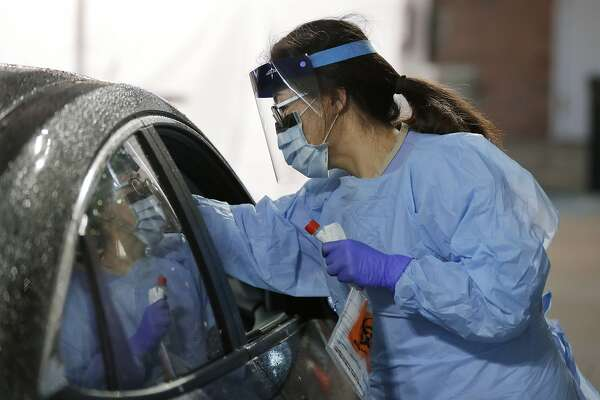 A nurse at a drive-up coronavirus testing station set up by the University of Washington Medical Center uses a swab to take a sample from the nose of a person in a car Friday, March 13, 2020, in Seattle. UW Medicine is conducting drive-thru testing in a hospital parking garage and has screened hundreds of staff members, faculty and trainees for COVID-19. U.S. hospitals are setting up triage tents, calling doctors out of retirement, guarding their supplies of face masks and making plans to cancel elective surgery as they brace for an expected onslaught of coronavirus patients. (AP Photo/Ted S. Warren)