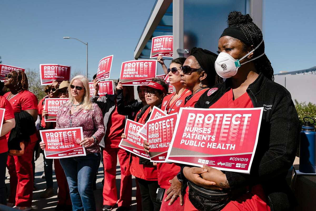 Registered nurses including Charlene Allen, left, hold signs as they rally during a national day of action held by National Nurses United in conjunction with the California Nurses Association in front of Sutter Health's Alta Bates Summit campus in Oakland, California, on Tuesday, March 11, 2020.