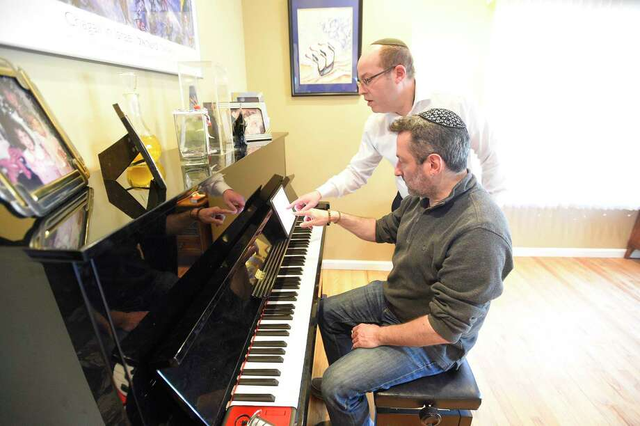 Rabbi Daniel Cohen and Jonathan Cahr of Stamford broadcast a Virtual Shabbat service for congregants of Congregation Agudath Sholom via a Facebook Live at the Rabbi's Stamford, Connecticut home on March 13, 2020. The Stamford Synagogue has closed its doors for the next several weeks, canceling all planned events and asking its congregants to self worship and pray, as the nation deals with the COVID-19 Coronavirus Pandemic. The telecast of the service brought approximately 40 viewers with many commenting to thank the Rabbi for providing this unique perspective. Photo: Matthew Brown, Hearst Connecticut Media / Stamford Advocate