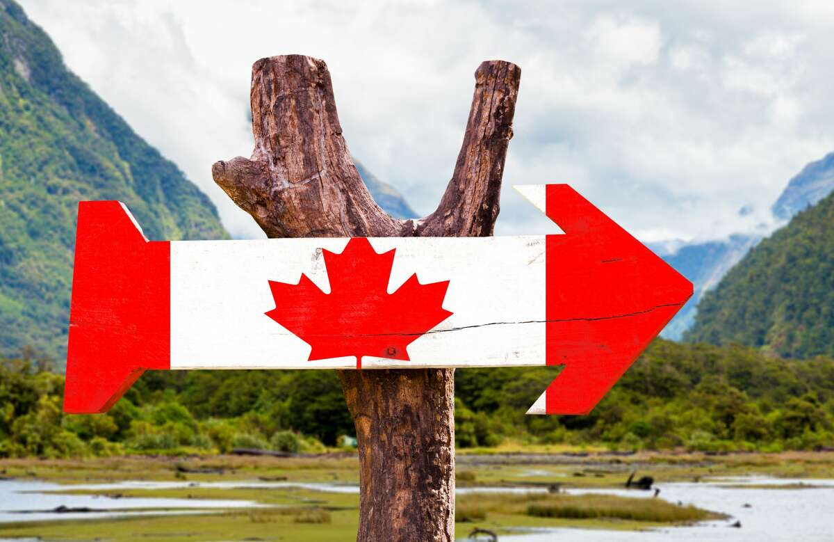Canada wooden sign with mountains background.