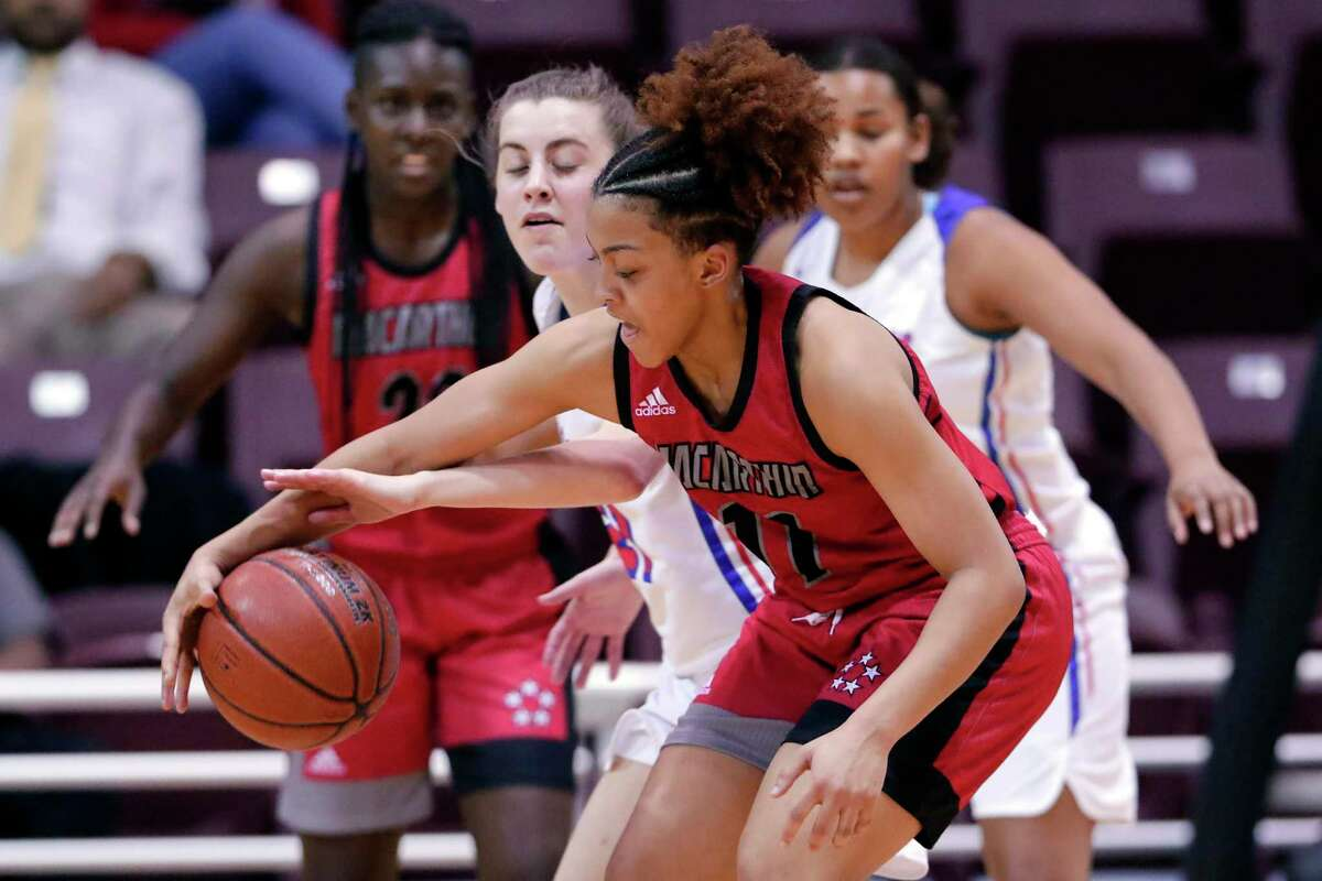 Oak Ridge guard Maddie Morris, left, reaches in to attempt to strip the ball from MacArthur guard Jada Stewart (11) during the first half of a Region II-6A bi-district playoff game at the Campbell Center Tuesday, Feb. 18, 2020 in Houston, TX.