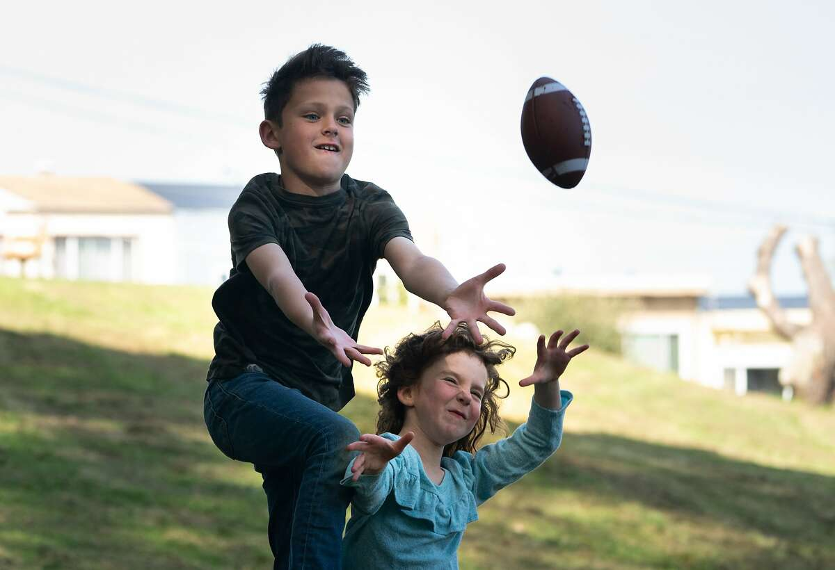 Kalim Campbell, 10, and sister Layli, 6 plays catch with their mother Lisa in a park near their home. The parents now must work from home, the children taught online due to concerns of the spread of the coronavirus on Friday, March 13, 2020, in San Francisco, Calif.