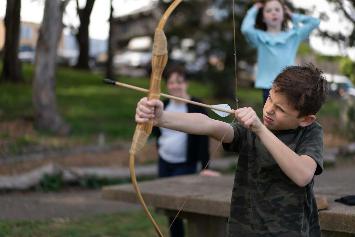 Kalim Campbell, 10, aims an arrow as mother Lisa and Layli, 6, watch at McLaren Park. The parents must work from home, the children taught online due to concerns of the spread of the coronavirus on Friday, March 13, 2020, in San Francisco, Calif.