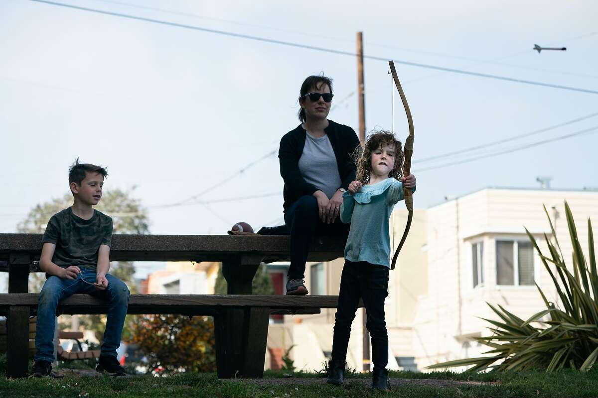 Layli Campbell, 6, shoots and arrow as Kalim, 10, left, and mother Lisa watches at McLaren Park, Lisa and husband Chris must work from home, the children taught online due to concerns of the spread of the coronavirus on Friday, March 13, 2020, in San Francisco, Calif.