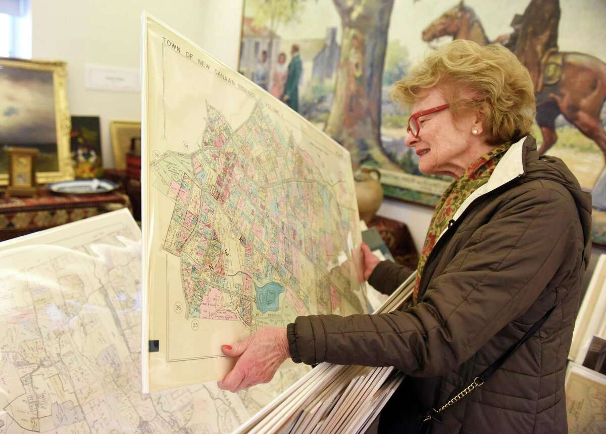 New Canaan resident Mimi Findlay looks at a 1938 map of New Canaan from Paper Duck Antiques at the recent New Canaan Art, Antique and Jewelry Show.