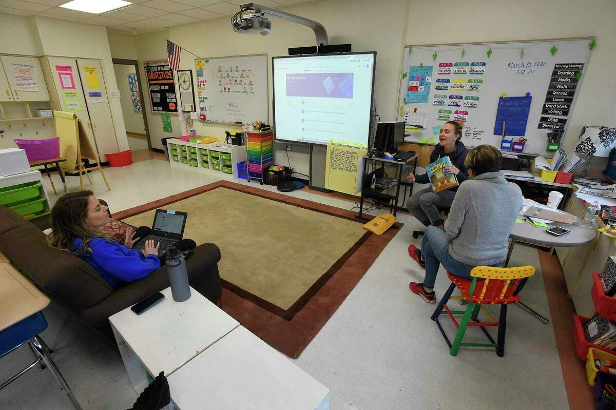 Alex Frattaroli, a third grade teacher at Julia A. Stark School in Stamford, Connecticut on March 13, 2020 sits on a couch upload digital mathematics lesson plans while fellow teaches Melissa Wall and Stacey Wood collaborate on their Virtual Lesson plans that students will use while the schools are closed for the next two weeks. the three teachers are preparing a Read Aloud, where they, as part of their lessons, each read a book via a video presentation for their students.