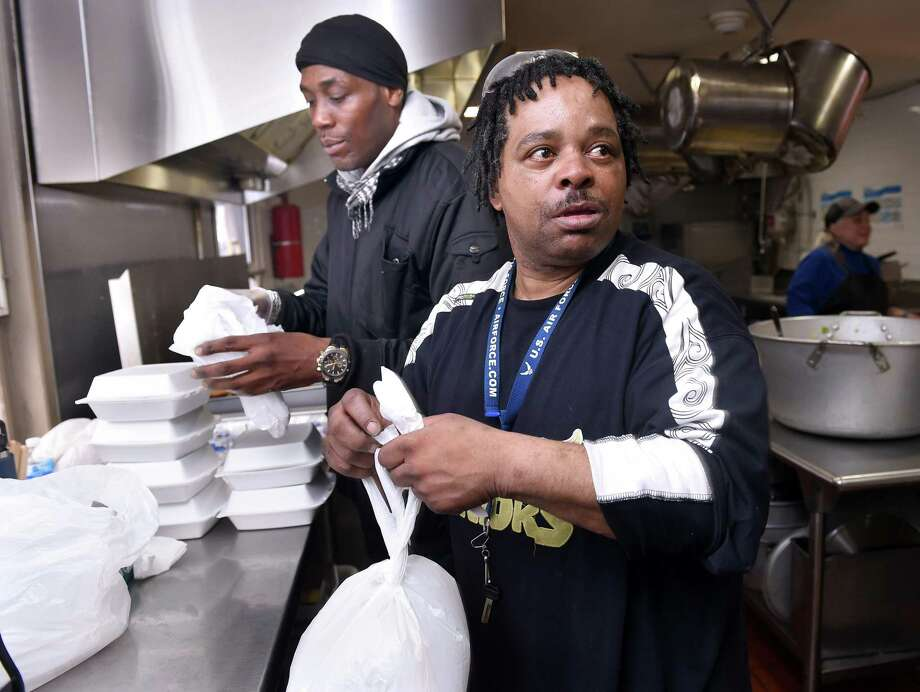 Sean Peterson (left) and Robert Jackson prepare takeout meals at the Community Soup Kitchen in New Haven on March 13, 2020. Photo: Arnold Gold / Hearst Connecticut Media / New Haven Register