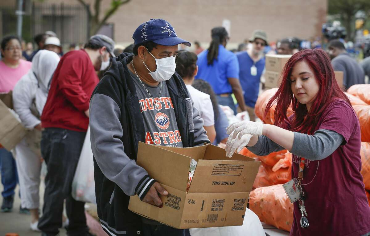 Jose Raudales wears a protective mask as he gets food during the Houston Independent School District along with the Houston Food Bank event that handed out food to hundreds of families in need Saturday, March 14, 2020, in Houston.