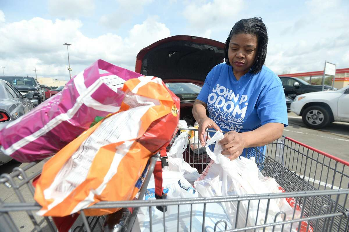 Jacqueline Ashford unloads a cart filled with supplies as she and daughter Dana Johnson join the shoppers filling lots at stores, including the H-E-B on College Street, to stock up in preparation for the potential spread of the coronavirus and quarantine conditions. Photo taken Friday, March 13, 2020 Kim Brent/The Enterprise