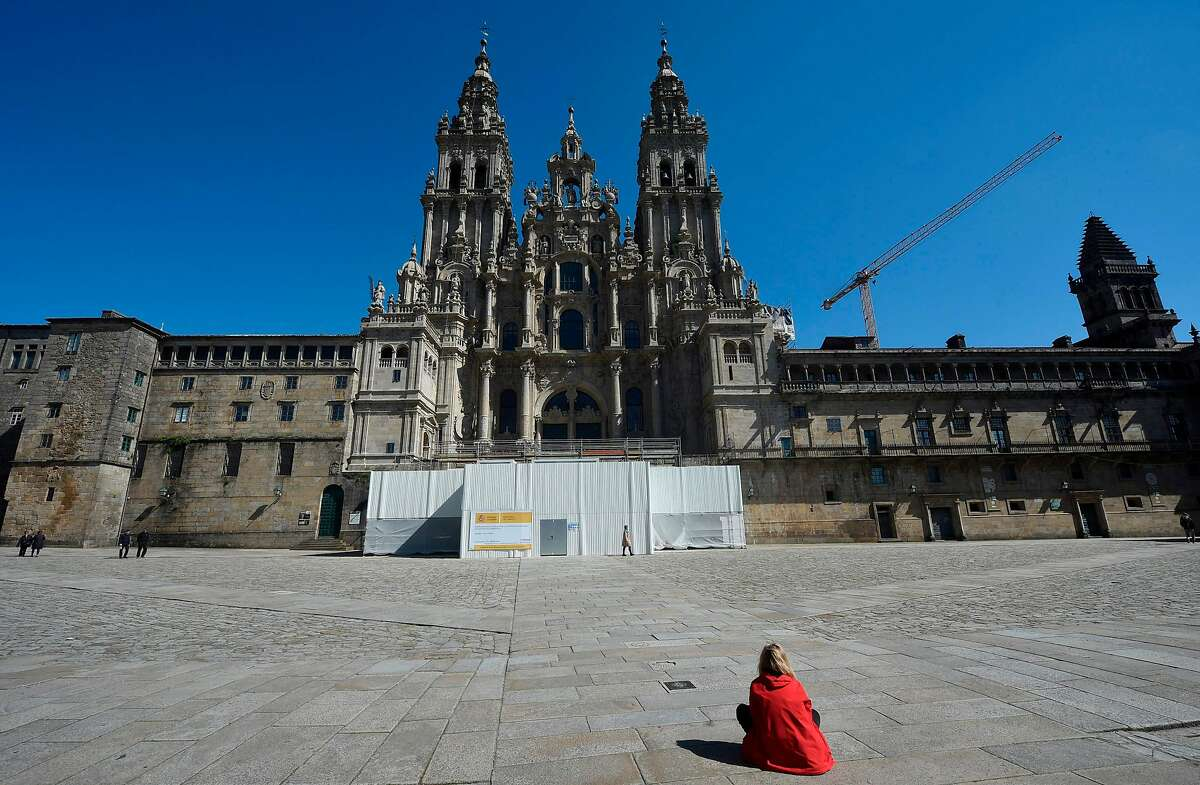 TOPSHOT - A woman sits outside the Santiago de Compostela Cathedral in the usually overcrowded Obradoiro Square in Santiago de Compostela on March 14, 2020 after regional authorities ordered all shops in the region be shuttered from today through March 26, save for those selling food, chemists and petrol stations, in order to slow the coronavirus spread. (Photo by MIGUEL RIOPA / AFP) (Photo by MIGUEL RIOPA/AFP via Getty Images)