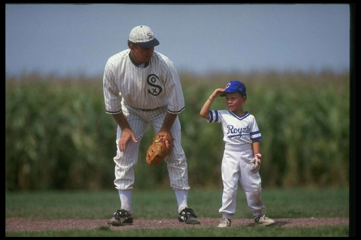 """A """"ghost player"""" recreating the role of Chicago White Sox legend Shoeless Joe Jackson plays ball with a young tourist at the baseball field created for the motion picture """"Field of Dreams."""""""