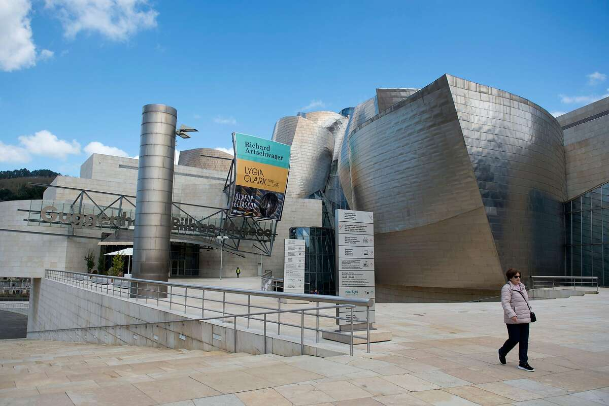A woman walks past the usually overcrowded Guggenheim Bilbao Museum in the Spanish Basque city of Bilbao on March 14, 2020 as Spain confirmed more than 1,500 new cases of coronavirus between Friday and Saturday raising its total to 5,753 cases, the second-highest number in Europe after Italy. - The country is expected to declare a state of alert to try to mobilise resources to combat the virus, which has so far killed 136 people in Spain. (Photo by ANDER GILLENEA / AFP) (Photo by ANDER GILLENEA/AFP via Getty Images)