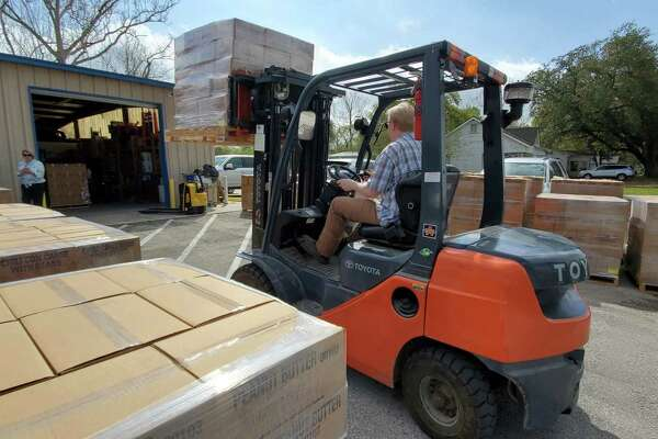 Volunteers from the Church of Jesus Christ of Latter-day Saints unload 50,000 pounds of food donations for the Humble Area Assistance Ministries.