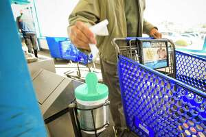 "A container of sanitizer wipe to clean hands and wipes surfaces of shopping carts is available at the entrance for customers shopping at the Shop Rite Market in Stamford, Connecticut on March 14, 2020. With the outbreak of the COVID-19 Coronavirus, Owner Tom Cingari and his staff have taken a pro-active approach, setting up hand sanitizing stations through out the store for customers to use. Providing protecting gloves for use by staff as well as customers. Cleaning ""Touch Points"" more frequently, such as areas around their Hot and Cold Buffet's, changing out serving spoons and wiping down surfaces throughout the store, in an attempt to limit customer exposure while they shop."