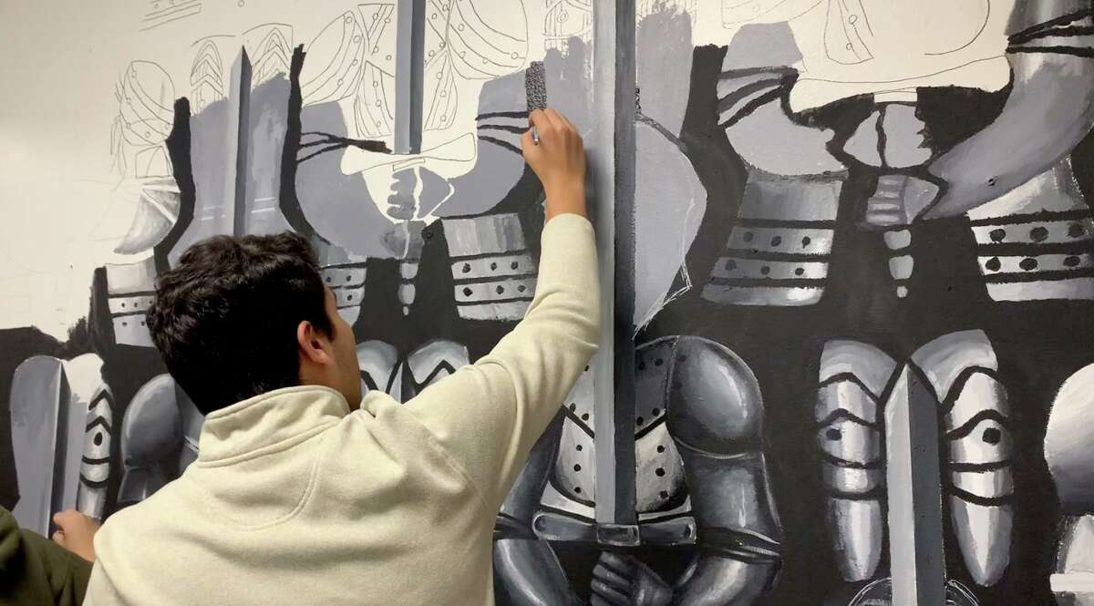 A member of the National Art Honors Society works on a mural at Stamford High School that was started in 2015 by a student.