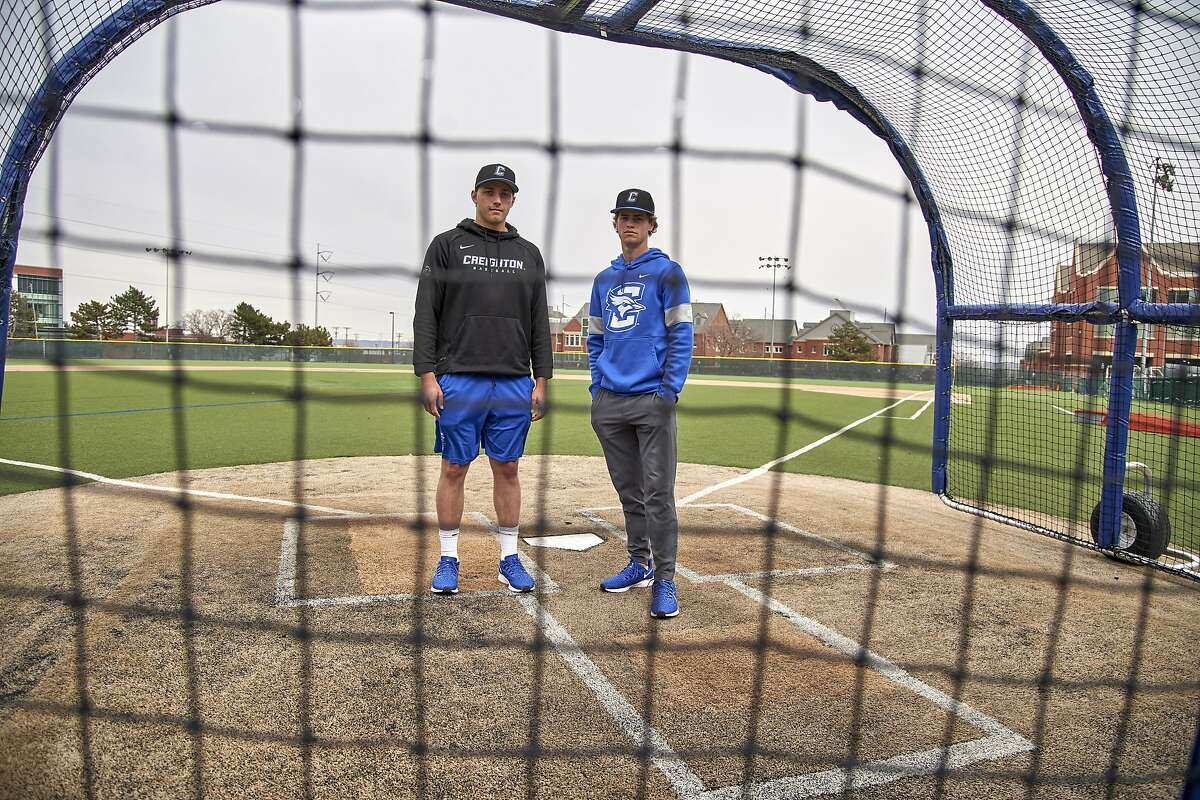 In this March 13, 2020 photo, Creighton NCAA college baseball pitchers Ben Dotzler and Tommy Steier, right, pose for a photo at home plate in Omaha, Neb. Dotzler was supposed to be in the bullpen at TD Ameritrade Park this weekend readying himself to pitch against Northern Colorado, Everything changed for hm and thousands of other college athletes when the NCAA announced March 12, 2020, it was canceling all spring sports championships, along with remaining winter championships, as a precaution against the spread of the new coronavirus. (AP Photo/Nati Harnik)