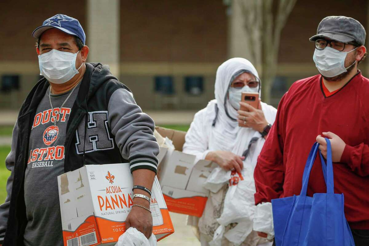 Jose Raudales ( left-right ) Dr. Amada Canales and Haryie Garrigues wear protective masks as they wait to get food during the Houston Independent School District along with the Houston Food Bank handed out food to hundreds of families in need Saturday, March 14, 2020, in Houston.