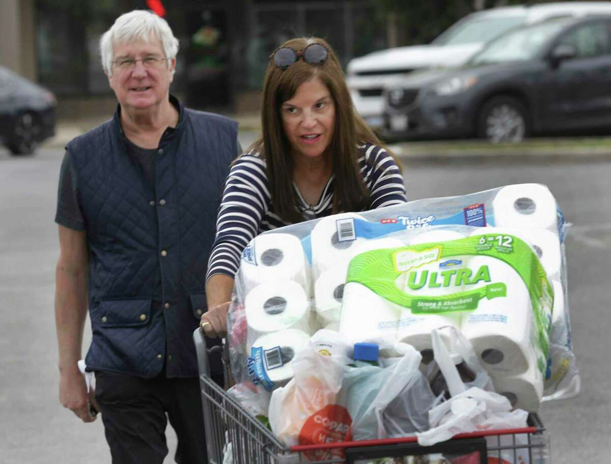 Diane Blank and her husband, Steven, push their full cart to their car after shopping.