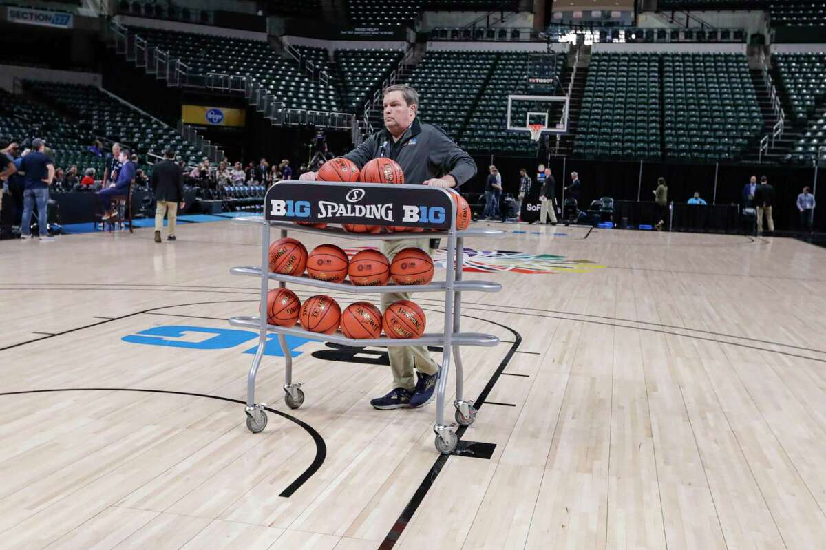 Basketballs are removed from the court at Bankers Life Fieldhouse, in Indianapolis, Thursday, March 12, 2020, after the Big Ten Conference announced that remainder of the men's NCAA college basketball games tournament was canceled.