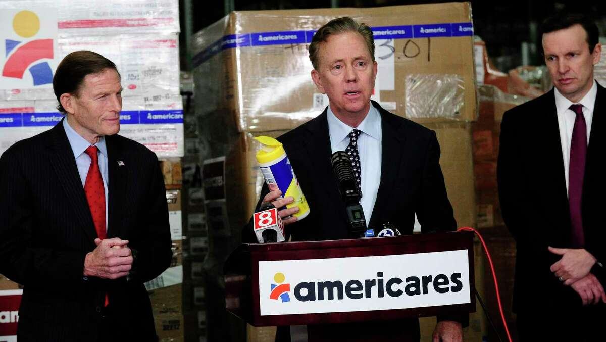 Governor Ned Lamont and U.S. Senators Richard Blumenthal and Christopher Murphy visit Americares' headquarters and global distribution center to receive an update on the health-focused relief and development organization's response to the COVID-19 pandemic on March 13, 2020 in Stamford, Connecticut. The governor holds a container of cleaning wipes as he speaks with the media.