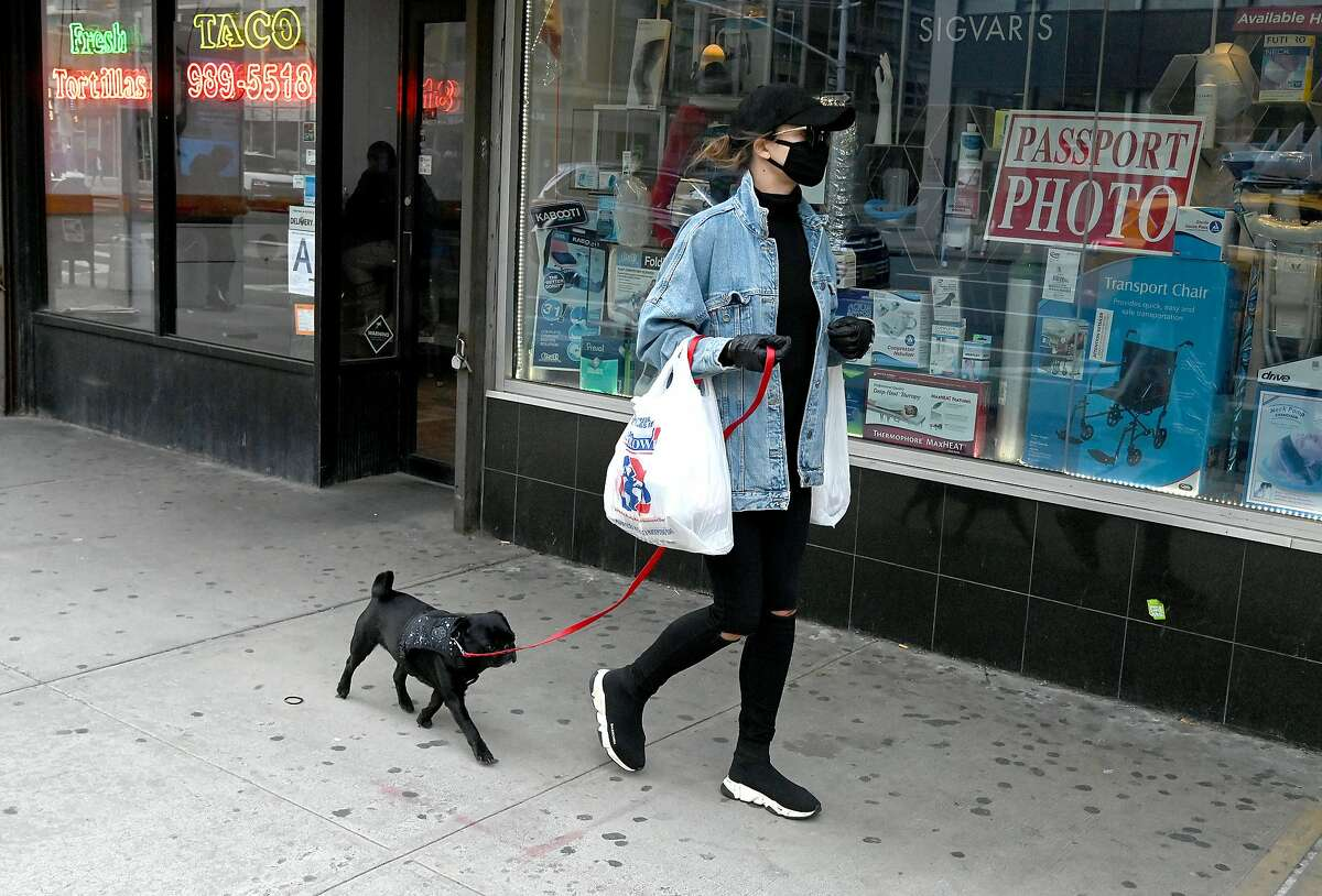 A person wearing a mask is seen walking their dog as the coronavirus continues to spread across the United States on March 14, 2020 in New York City. The World Health Organization declared coronavirus (COVID-19) a global pandemic on March 11th. (Photo by Jamie McCarthy/Getty Images)