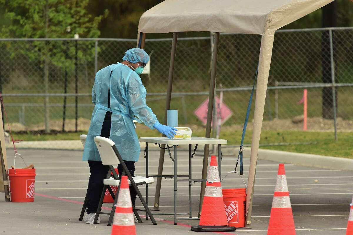 A medical technician prepares for the arrival of people who have orders to be tested for the novel coronavirus at the new drive-through testing facility at the Texas Medical Center on Saturday, March 14, 2020. Doing the testing outside makes it less likely that the virus could be spread.