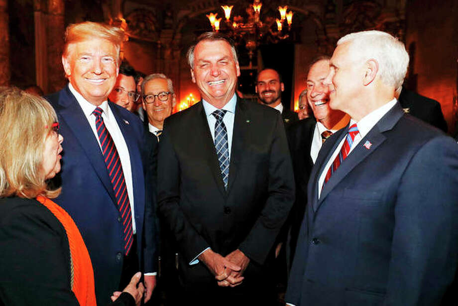 In this March 7, 2020, photo provided by Brazil's presidential press office, Brazil's President Jair Bolsonaro, center, stands with President Donald Trump, second from left, Vice President Mike Pence, right, and Brazil's Communications Director Fabio Wajngarten, behind Trump partially covered, during a dinner in Florida. Wajngarten tested positive for the new coronavirus, just days after the trip, according to Bolsonaro's communications office on Thursday, March 12, 2020.