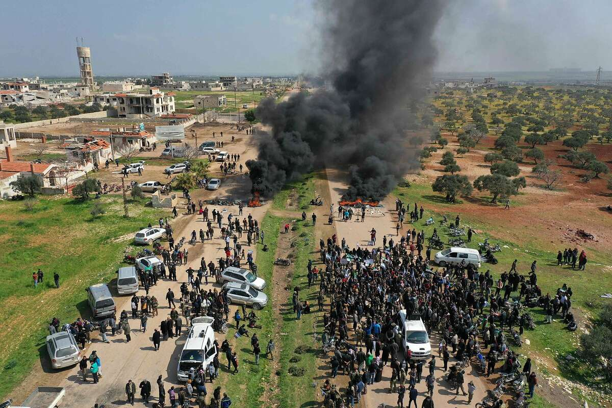 Syrians protest and burn tyres in an attempt to block traffic on the M4 highway, which links the northern Syrian provinces of Aleppo and Latakia, before incoming joint Turkish and Russian military patrols (as per an earlier agreed upon ceasefire deal) in the village of al-Nayrab, about 14 kilometres southeast of the city of Idlib and seven kilometres west of Saraqib in northwestern Syria on March 15, 2020. - Russian President Vladimir Putin and his Turkish counterpart Recep Tayyip Erdogan reached a deal on March 5 to create a security corridor with joint Turkish and Russian patrols starting on March 15 along the key M4 highway in northern Syria, which runs roughly parallel to the border with Turkey, from northeastern Kurdish-controlled regions to the Mediterranean coast. (Photo by Omar HAJ KADOUR / AFP) (Photo by OMAR HAJ KADOUR/AFP via Getty Images)