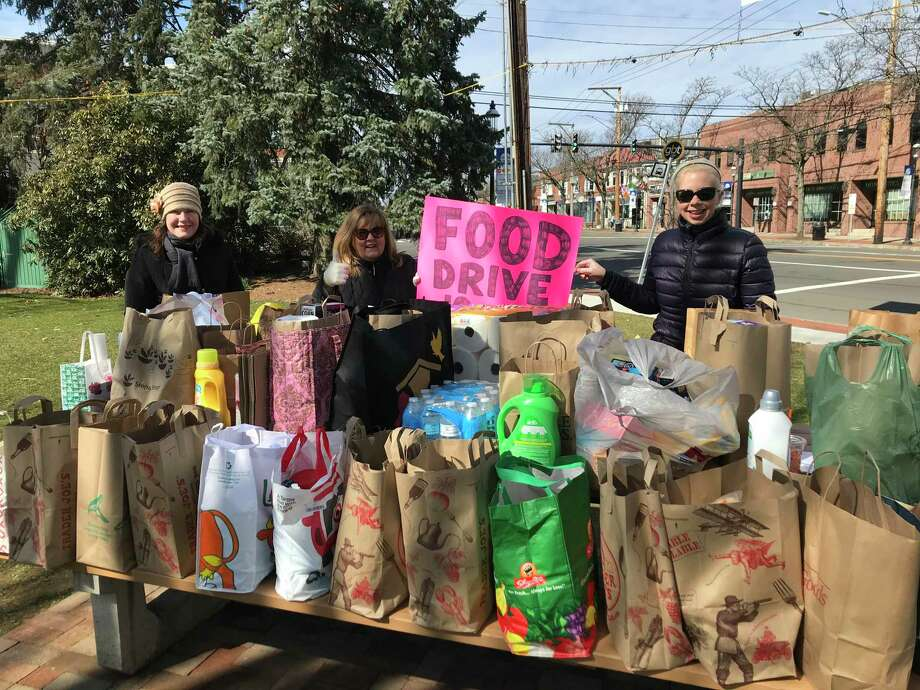 Organizers Helene Daly, Heather Dubrosky, and Alexis Harrison gather food and supplies for those affected by the coronavirus on the Fairfield green Sunday, March 15. Photo: /