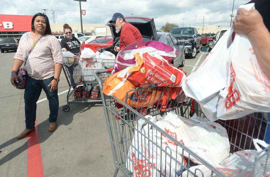 Jacqueline Ashford unloads a cart filled with supplies as she and daughter Dana Johnson (left) join the shoppers filling lots at stores, including the H-E-B on College Street, to stock up in preparation for the potential spread of the coronavirus and quarantine conditions. Photo taken Friday, March 13, 2020 Kim Brent/The Enterprise Photo: Kim Brent/The Enterprise