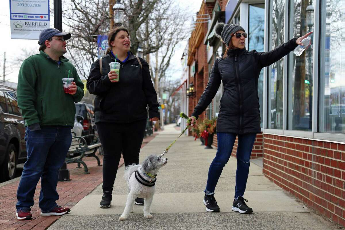 From left, Zach Arguin of Amesbury, Mass., Brittni Colon and Sue Colon and their dog Max, all of Southport, do some window shopping on Saturday, March 14, 2020, in Fairfield, Conn.