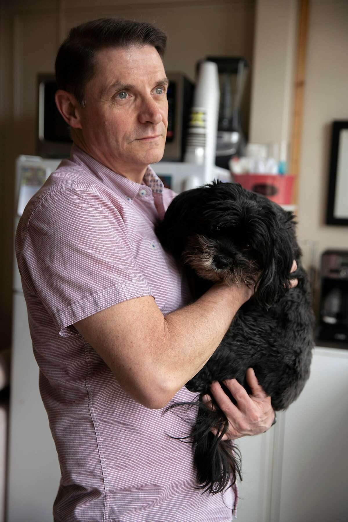 Curtis Bradford with his dog Maggie Mae at his home on Saturday, March 14, 2020, in San Francisco, Calif. Bradford, 55, is HIV positive and part of the population vulnerable to getting sick from the coronavirus. Bradford decided to self isolate on March 6, but has been struggling with the mental and emotional toll of being alone in an SRO without his usual work and community activities.