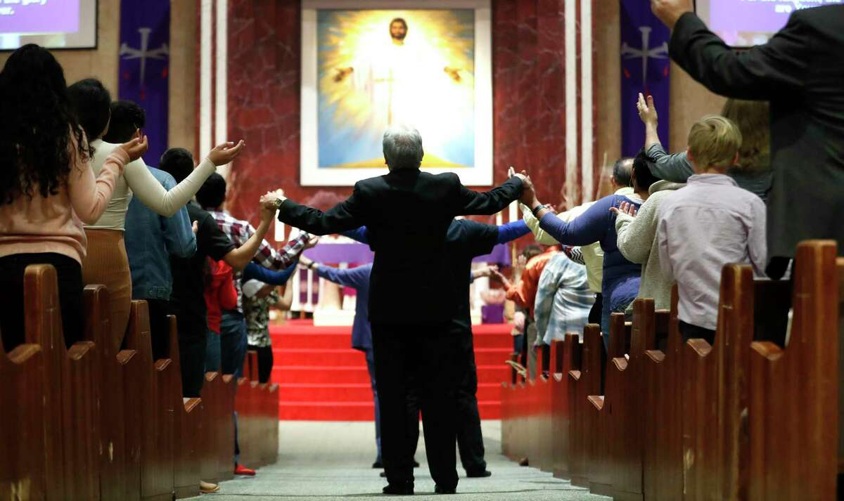 Worshippers hold hands across the aisles during Sunday mass at Catholic Charismatic Center 1949 Cullen, in Houston,Sunday, March 15, 2020. The church normally has as many as 1200 parishioners on Sundays, however, many people opted to watch it live-streamed, as fears of being in large groups may have kept people home.