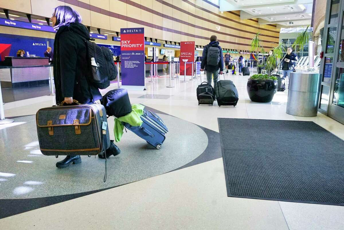 Air travelers make their way through the Albany International Airport on Sunday, March 15, 2020, in Colonie, N.Y. (Paul Buckowski/Times Union)