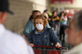 A shopper wears a masking while waiting to enter a Costco in the Bay Area city of Novato.