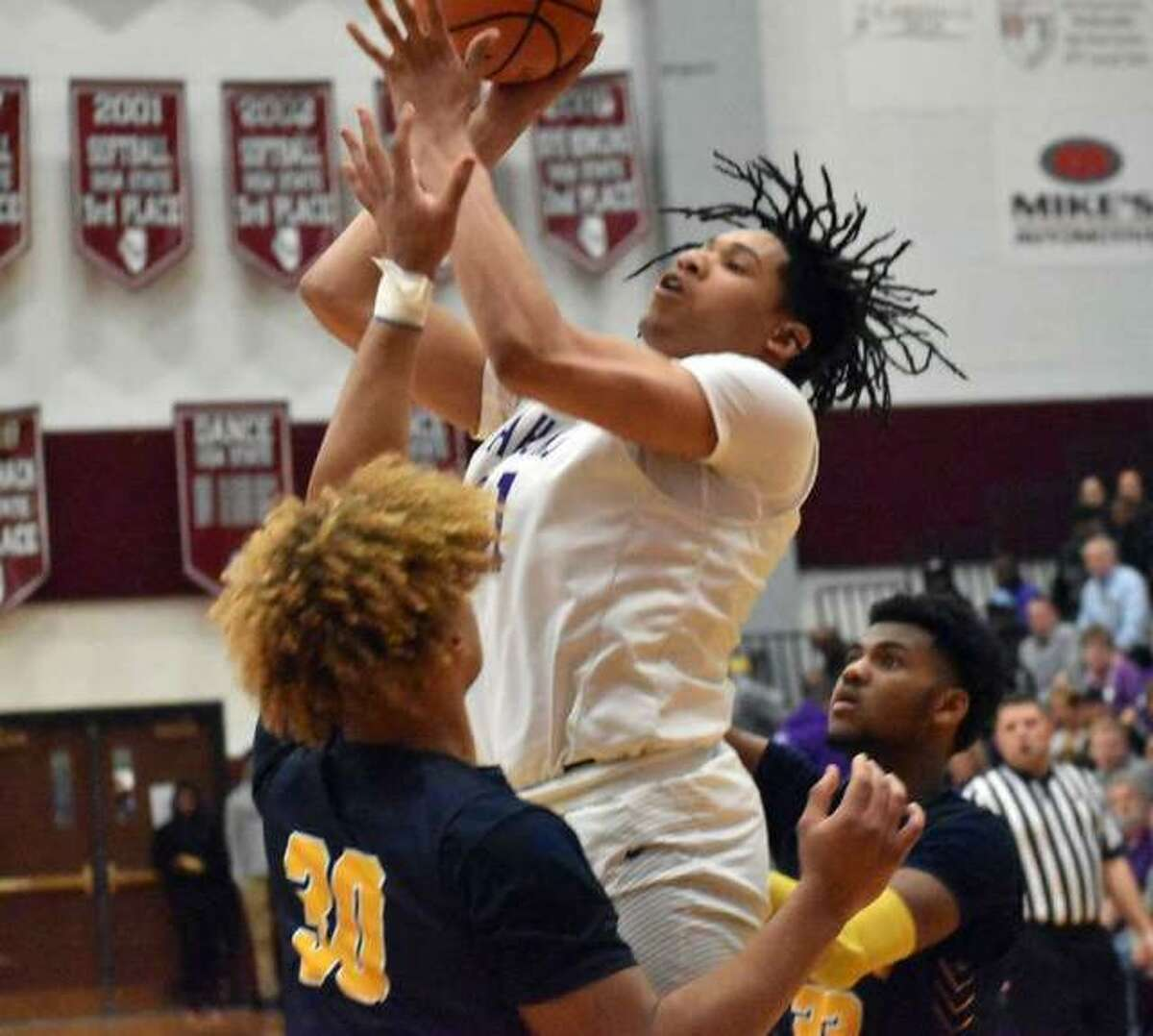 Collinsville senior forward Keydrian Jones hits a turnaround shot in the lane over O'Fallon's Dawson Algee in the first half of Tuesday's Class 4A sectional semifinat at Belleville West.