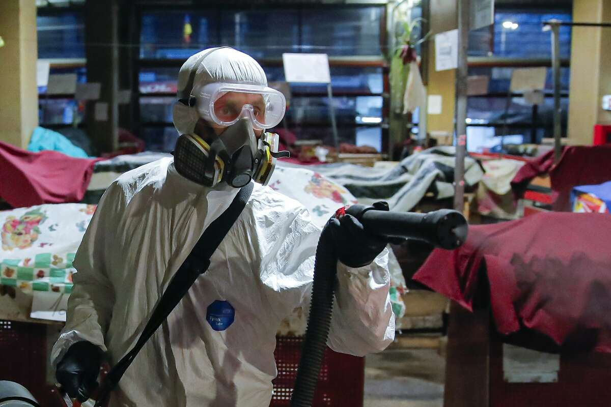 A man wearing protective gear sprays chemicals during the disinfection of a popular market, part of the efforts to limit the spread of the Coronavirus, in Bucharest, Romania, Sunday, March 15, 2020. For most people, the new coronavirus causes only mild or moderate symptoms. For some it can cause more severe illness. (AP Photo/Vadim Ghirda)